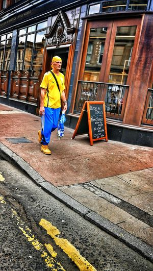 Full length portrait of man standing against yellow building