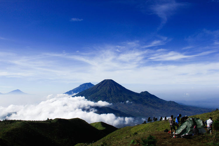 People Camping On Mountain Against Volcanic Crater
