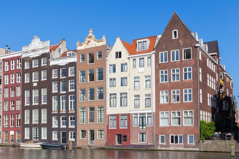 Damrak - Amsterdam in the Summertime - coloured canal houses Europe Trip Façade Dutch Culture Canal Houses Amsterdam Canal Holland Netherlands UNESCO World Heritage Site Amsterdam Building Exterior Architecture Built Structure Building Sky Window Clear Sky City House Sunlight Row House Day No People