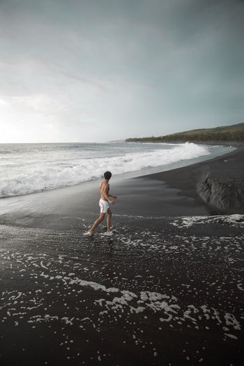 Full length of man walking on shore at beach