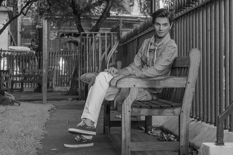 Full length of thoughtful young man sitting on bench by fence at park