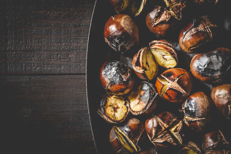 Close up of Roasted chestnuts in iron grilling pan over rustic wooden table, top view, copy space. Autumn Chestnut Chestnuts Cooking Iron Meal Snack Brown Food Fried Fruit Gourmet Healthy Heap Ingredient Nut Opened Pan Roasted Roasting Seasonal Sweet Tasty Traditional Wooden