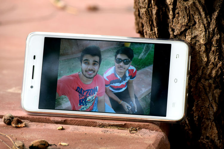 Mobile phone with photograph of young friends sitting on retaining wall