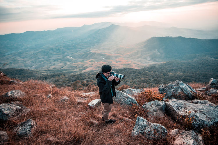 Man Photographing Through Camera While Standing On Mountain Against Sky During Sunset