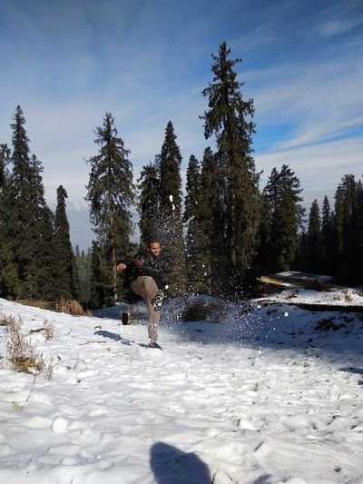 Man kicking snow on land against sky