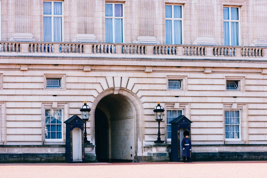 A guard dressed in blue standing in front of the Buckingham Palace in London, United Kingdom. Architecture Buckingham Palace Building England Façade Guard London Outdoors Royal United Kingdom