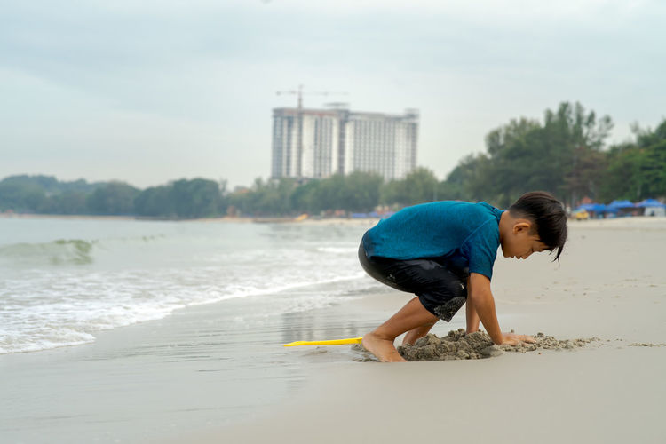 Side view of boy playing with sand at beach