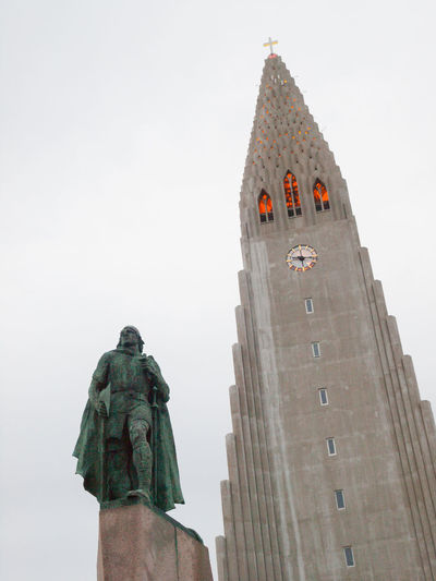 The statue of explorer Leif Ericsson. Hallgrímskirkja is a Lutheran (Church of Iceland) parish church in Reykjavík, Iceland. At 73 metres (244 ft), it is the largest church in Iceland and among the tallest structures in Iceland. The church is named after the Icelandic poet and clergyman Hallgrímur Pétursson (1614 to 1674), author of the Passion Hymns.Situated in the centre of Reykjavík, it is one of the city's best-known landmarks and is visible throughout the city. State Architect Guðjón Samúelsson's design of the church was commissioned in 1937. He is said to have designed it to resemble the basalt lava flows of Iceland's landscape. The design is similar in style to the expressionist architecture of Grundtvig's Church of Copenhagen, Denmark, completed in 1940. Leif Eriksson Reykjavik Architecture Army Army Soldier Day Hallgrìmskirkja Hallgrímur Pétursson Iceland Memories Low Angle View Men Military One Person Only Men Outdoors Patriotism People Rear View Tourism Tourist Attraction  Travel Viking Vivid International