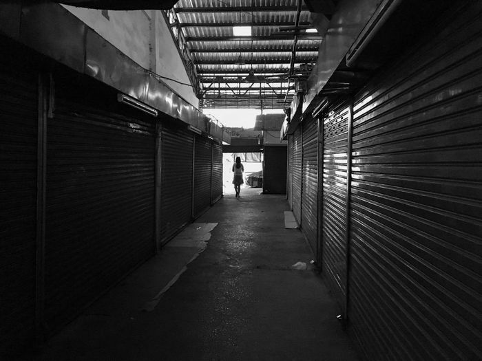Rear view of woman walking in alley amidst closed shops