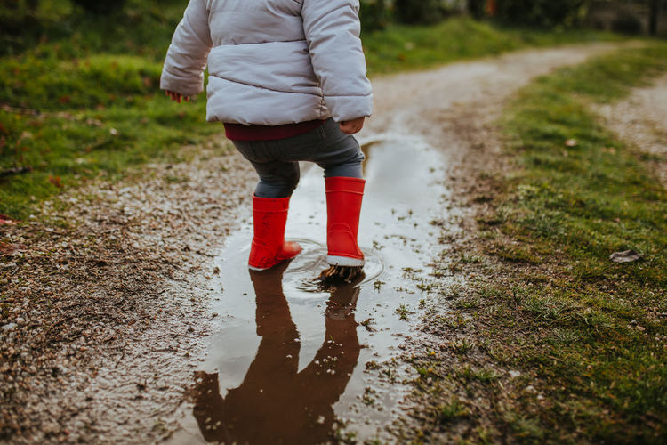 Low section of baby girl standing on puddle during rainy season