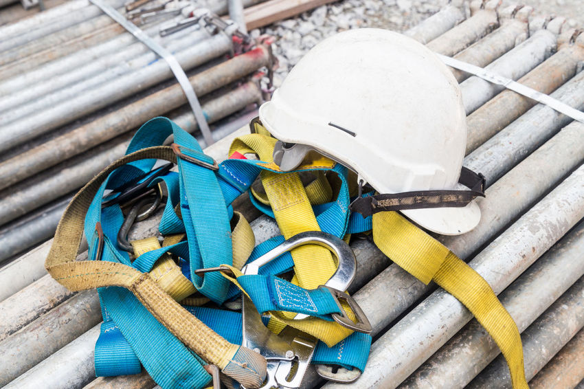 Safety helmet and harness at construction site Construction Site Industry Safety Hard Hat Builders Close Up Dangerous Engineering Helmet No People Protective Workwear Regulation Safety Harness Tools