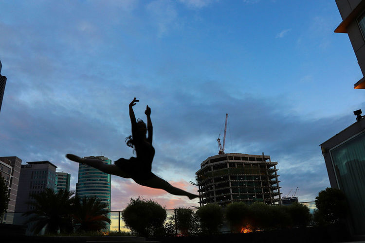 grand jete and sunset Ballerina Confidence  Inner Power Power Architecture Arms Raised Ballet Ballet Dancer Building Building Exterior Cloud - Sky Dancing Girl Grand Jete Highjump Innerstrength Jumping Mid-air Office Building Exterior One Person Silhouette Sky Sunset