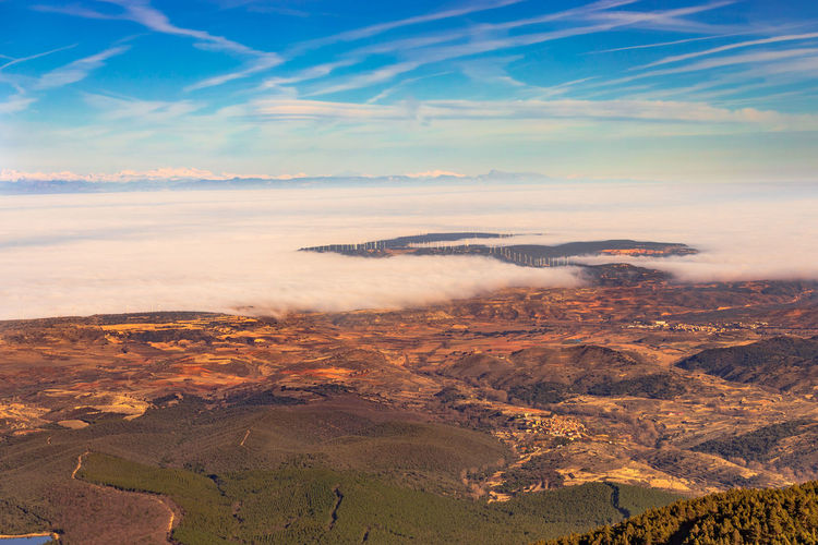 High angle view of cloud-filled valley against mountains and sky during sunset