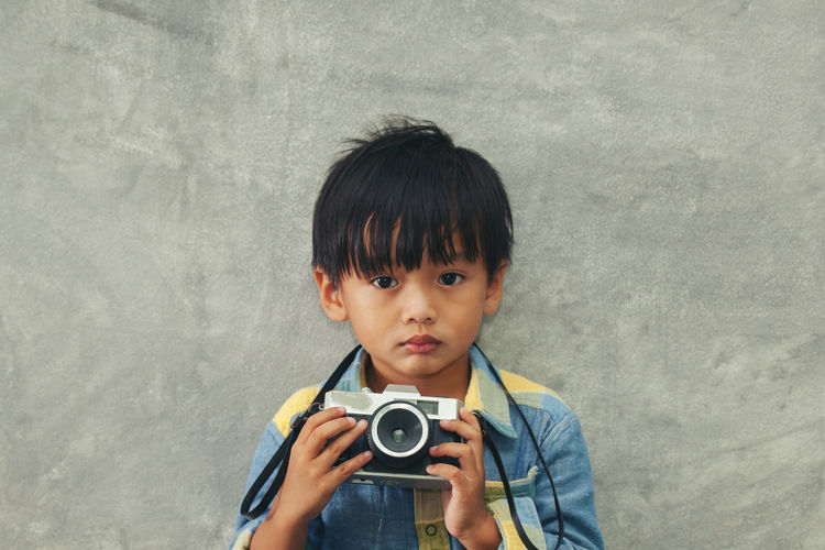 Portrait of boy holding camera while standing against wall