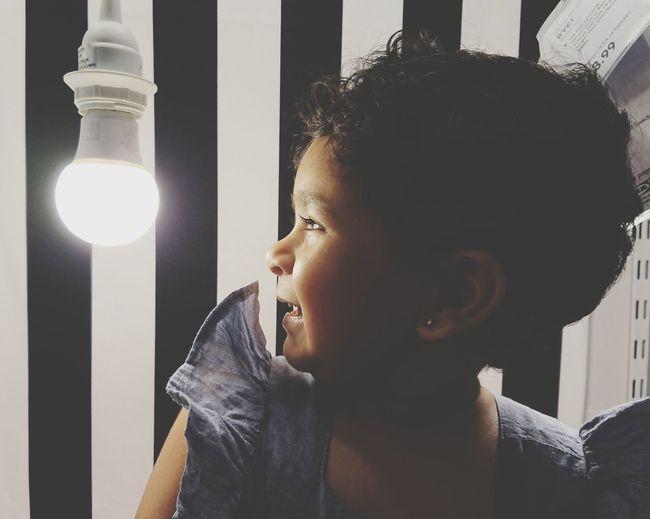 Close-Up Of Smiling Baby Girl Looking At Illuminated Light Bulb