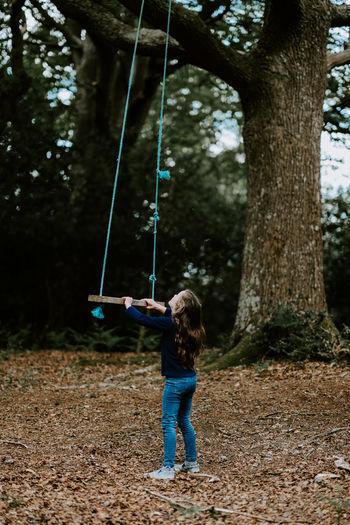 Full length of girl standing by swing