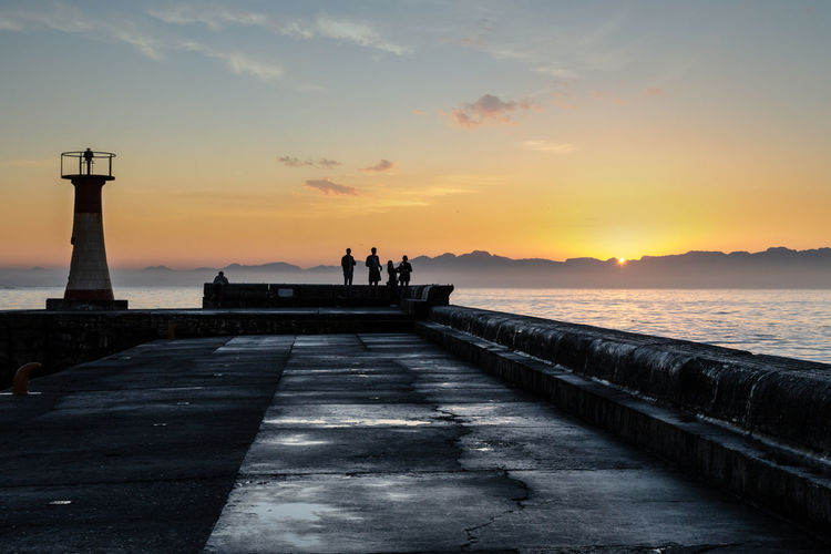 Silhouette people on pier by sea against sky during sunset