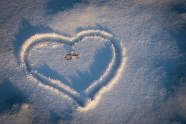 High angle view of heart shape in snow with golden wedding rings