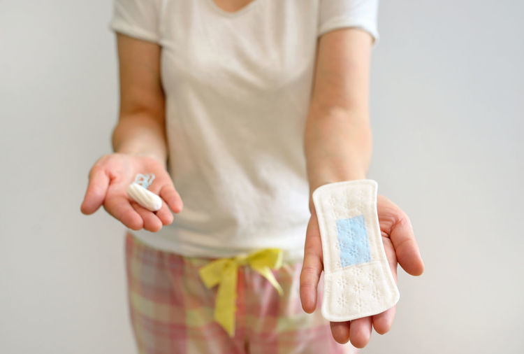 Midsection of woman holding tampon and sanitary pad
