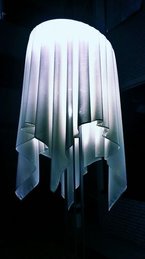 Low Angle View Of White Fabric On Pendant Light In Darkroom