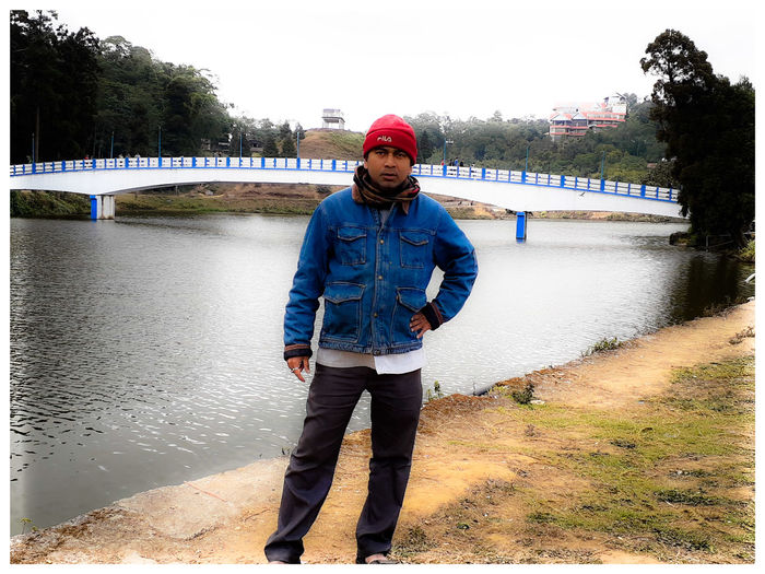 Portrait of young man standing on bridge over canal