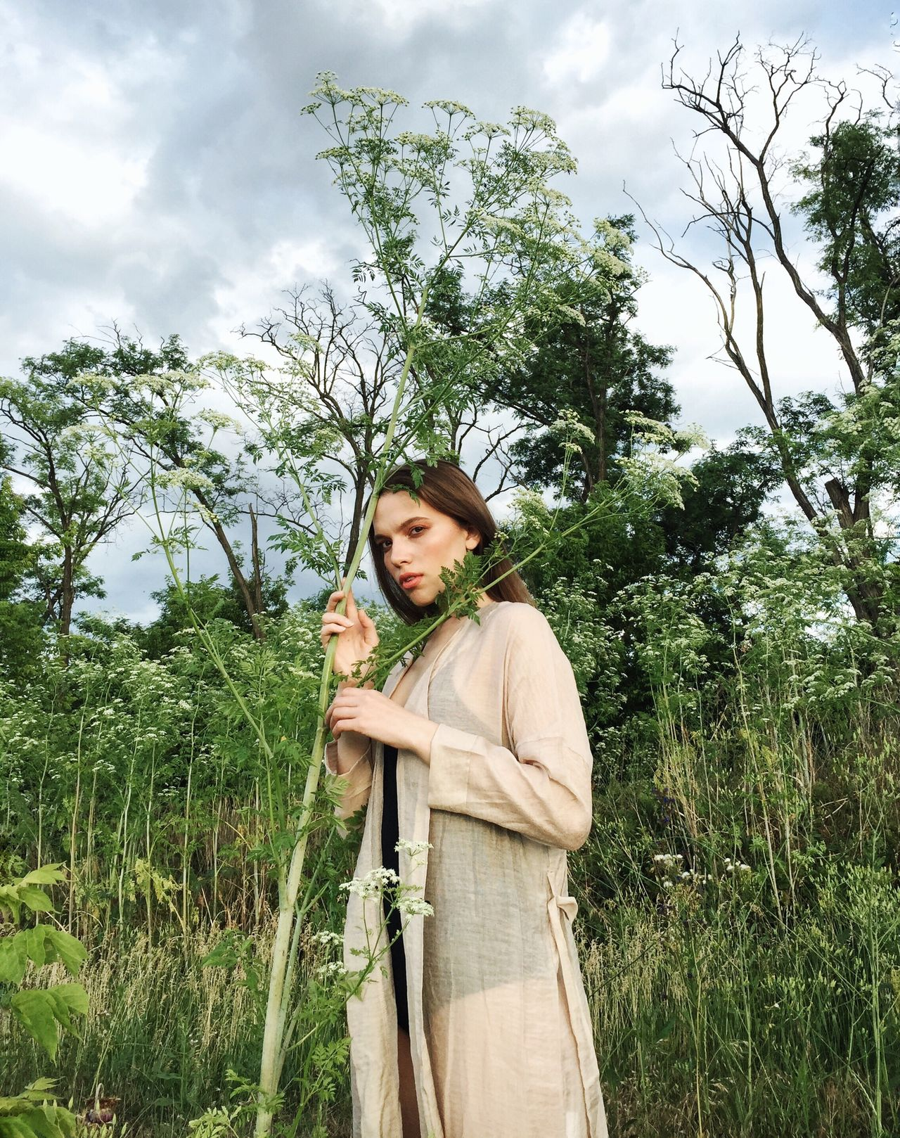 Portrait of woman standing by plant against sky