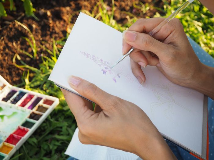 High angle view of woman hand painting on paper in park