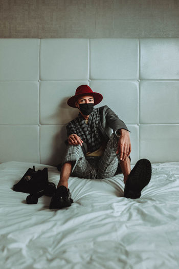 Full length of young man sitting on bed against wall