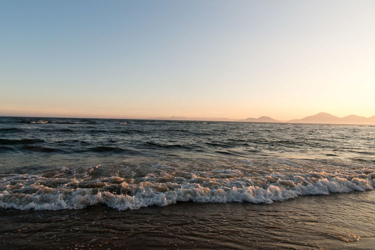 Aquatic Sport Beach Beauty In Nature Clear Sky Copy Space Horizon Horizon Over Water Land Motion Nature Outdoors Scenics - Nature Sea Sky Sport Sunset Surfing Water Wave