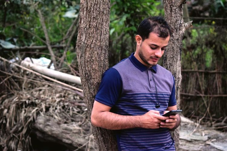 Young man using mobile phone while leaning on tree at forest