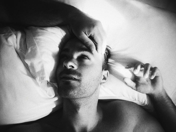 Cropped hand of gay man over male lying on bed
