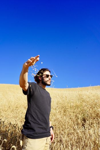 Man standing on field against clear blue sky