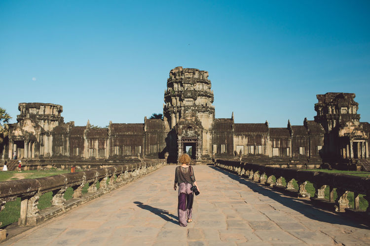 Rear View Of Woman Walking Towards Temple Against Blue Sky
