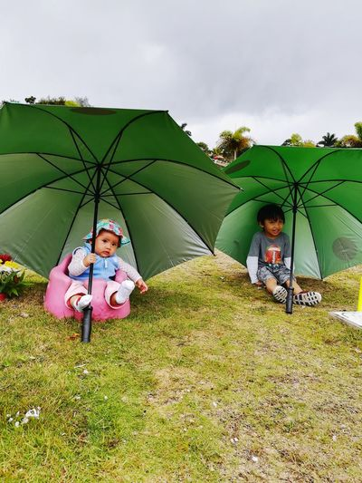 Children sitting under umbrellas while sitting on grassy field against cloudy sky