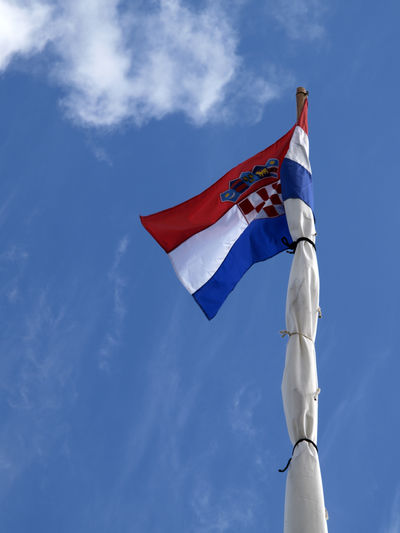 Low angle view of croatian flag against blue sky