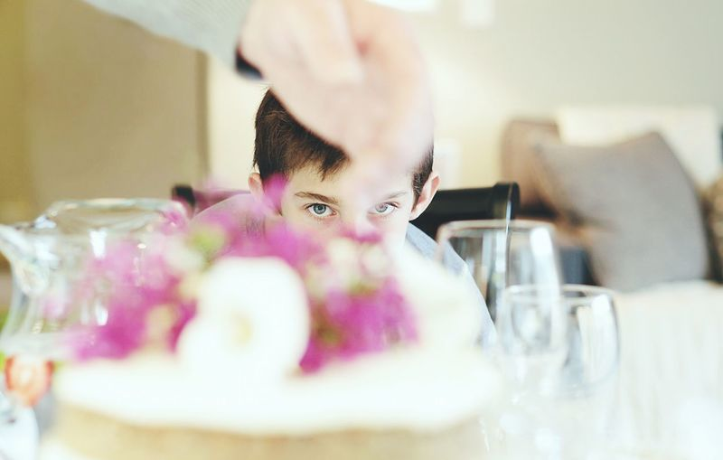 Portrait of boy seen through cake at table
