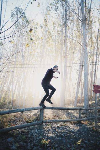 Forest Full Length One Person Lifestyles Outdoors Motion Standing Day Exercising Tree Bare Tree Real People Nature Young Adult Mammal People