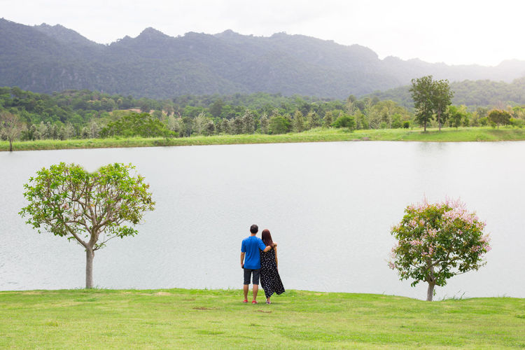 Behind of couple with tree heart shape on grass field , lake , mountain and tree . Romance seen Beauty In Nature Bonding Couple - Relationship Day Full Length Grass Lake Leisure Activity Love Nature Outdoors Plant Positive Emotion Rear View Scenics - Nature Togetherness Tranquil Scene Tranquility Tree Two People Water Women