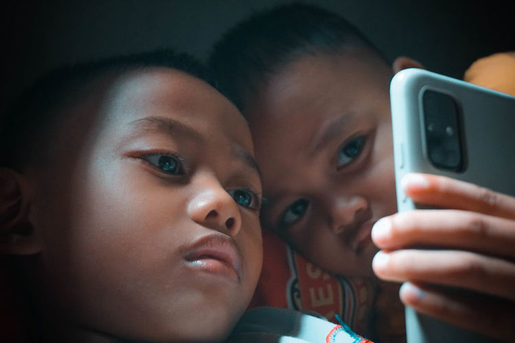 Close-up of brothers using smart phone at home