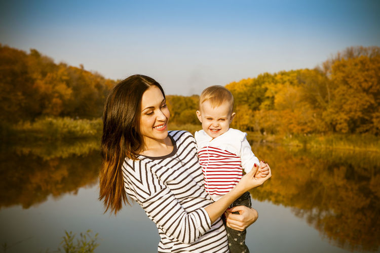 Mother holding daughter at lake during sunny day