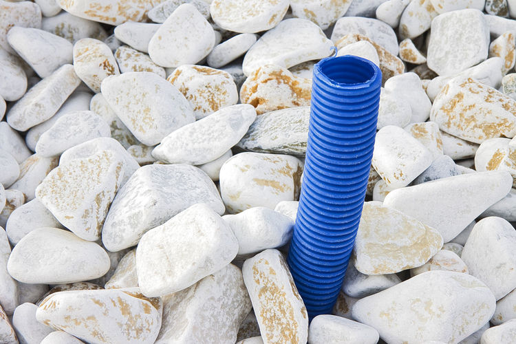 Plastic Pipe Pipeline Large Group Of Objects Solid Rock No People Stone - Object Rock - Object Day Still Life Stone Abundance High Angle View Metal Pebble Textured  Full Frame Backgrounds Nature Container Outdoors Spiral Concrete