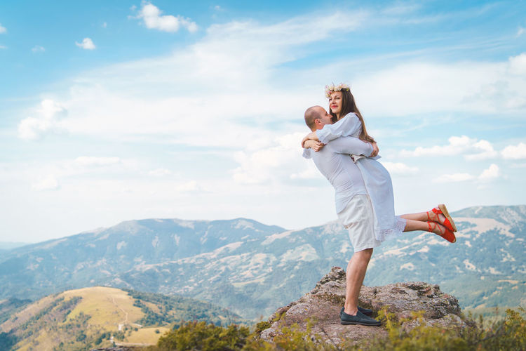 Male partner embracing female while standing on mountain against cloudy sky