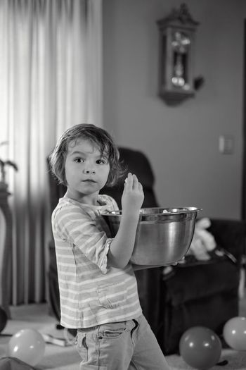 Side view of boy holding popcorn in large bowl at home