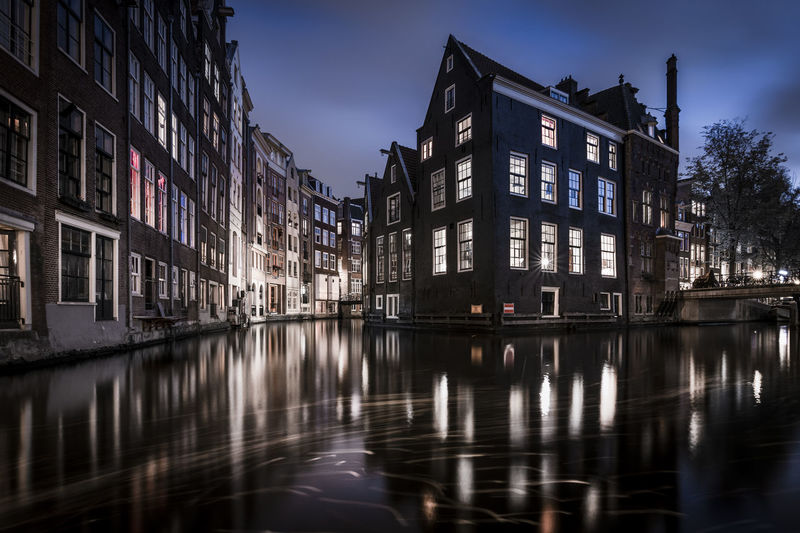 Reflection of illuminated buildings in river at dusk