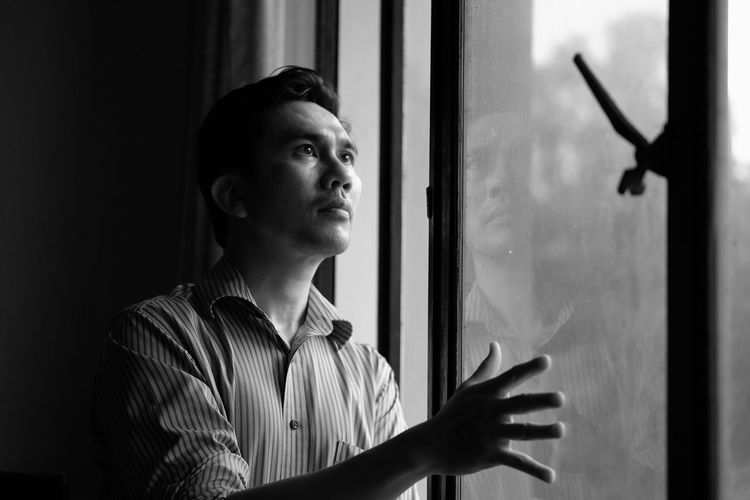 A man standing Real People One Person Indoors  Looking Through Window Young Adult Standing Lifestyles Day Young Women Close-up People Front View Portrait Selfportrait Self Portrait Touching Hand Adult Standing Indoors  Blackandwhite Black And White Monochrome Window Resist TCPM The Portraitist - 2017 EyeEm Awards