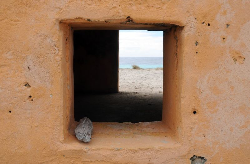 Beach View from slave home in Bonaire 1850's near Salt mines Beach Salt Slave Window Land Beach Sand Sea No People Nature Sky Old Scenics - Nature Abandoned Tranquility Tourism