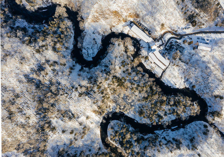 High angle view of river and houses snow covered field