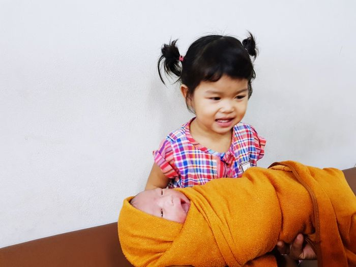 Cute girl carrying sister at home