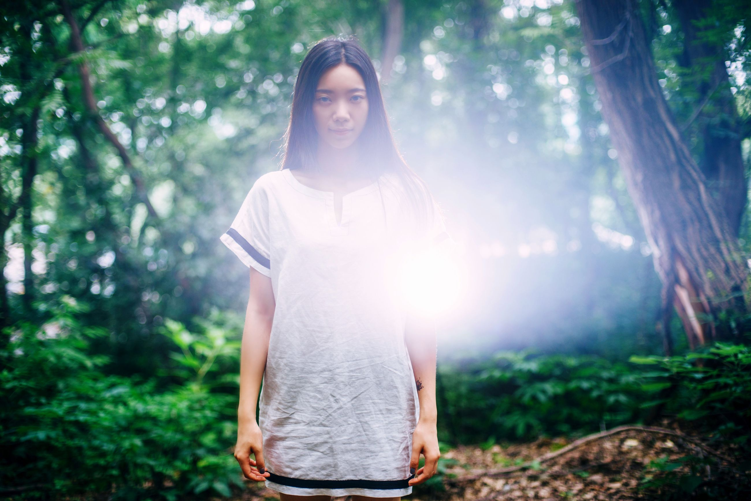 young adult, lifestyles, tree, leisure activity, forest, front view, person, casual clothing, young women, portrait, looking at camera, sunlight, sunbeam, standing, lens flare, focus on foreground, three quarter length