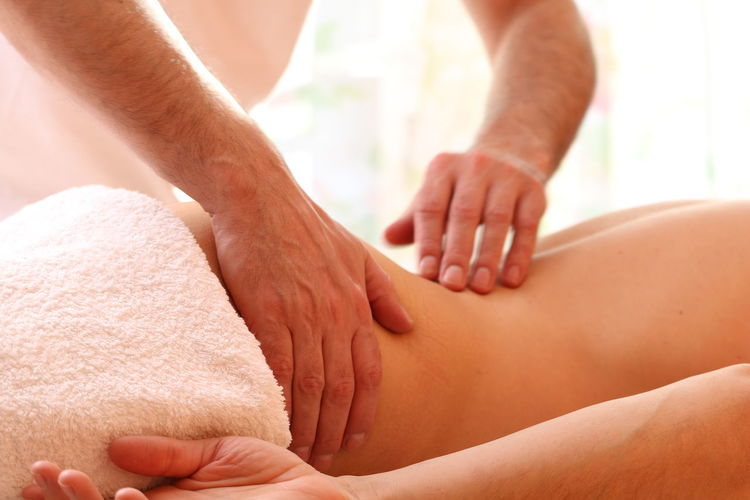 Midsection of therapist massaging woman at spa